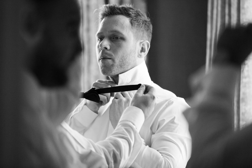 Black and white documentary wedding photography by Cheshire based wedding photographer. The groom wearing black tie.