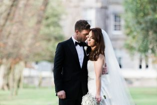 Bride in Suzanne Neville Gown and groom in black tie at a wedding at Carlowrie Castle in Edinburgh, Scotland