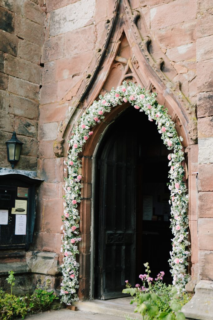 Acton Church in Nantwich with flower arch for a Dorfold Hall church wedding ceremony.