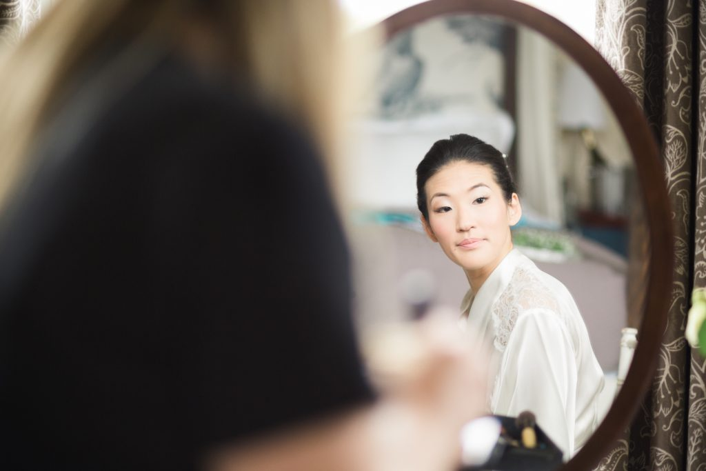Bride getting ready in the bridal suite at Iscoyd Park, Shropshire. Elegant, light and airy fine art wedding photography