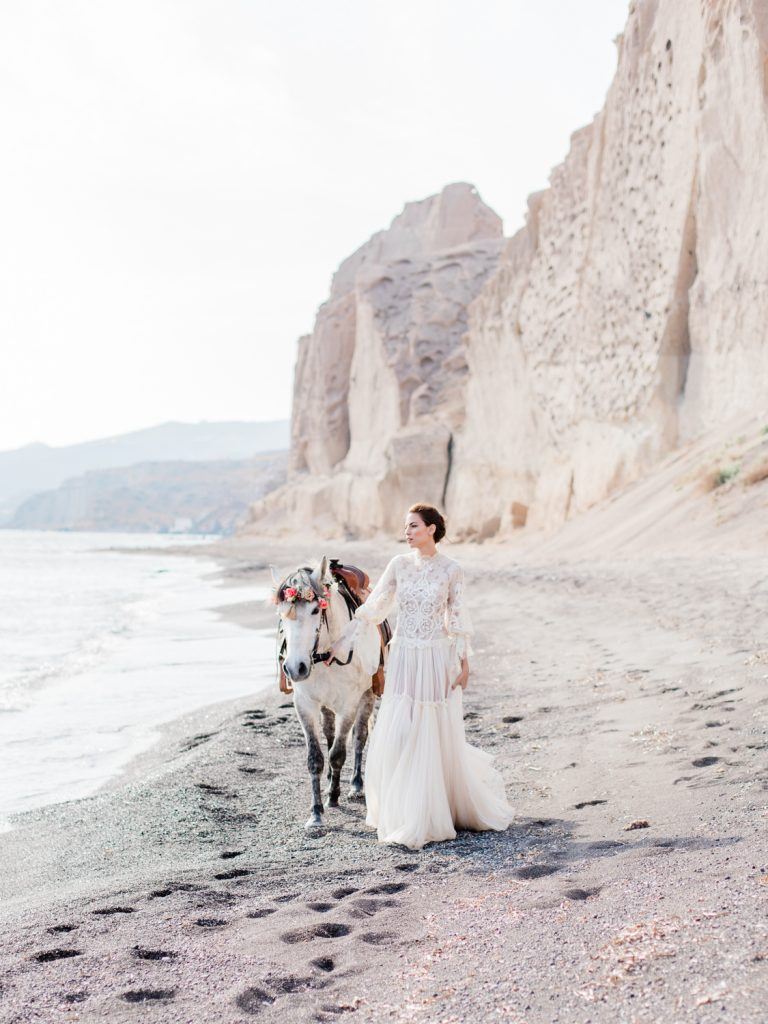 Santorini beach wedding editorial featuring white horse with floral crown
