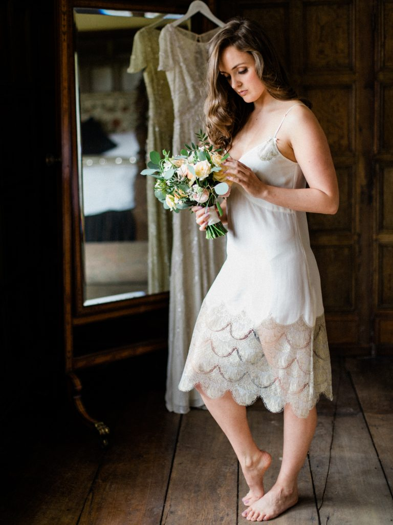 Bridal preparatrion at Dorfold Hall. Bride wearing Shell Belle Couture ivory lace and gold slip with bridal bouquet by Flowers by Breige.